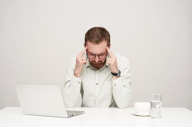疲れた若い剃っていない金髪のビジネスマンは、白い背景で隔離、ハードワークの日後に頭痛を抱えている間、こめかみに指を保ちます