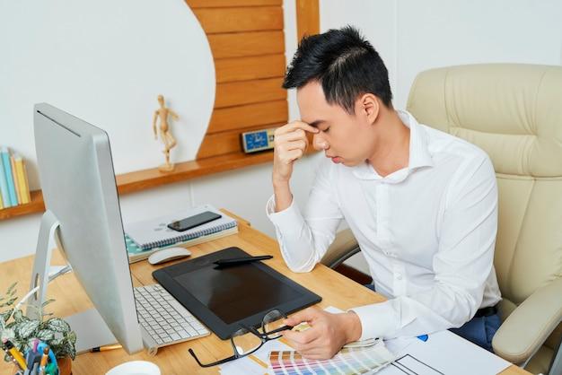 何時間もコンピューターで作業した後、頭痛を抱えている疲れた若いベトナムのグラフィックデザイナー