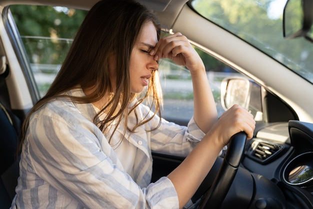 Tired young woman car driver suffer from headache or migraine pain inside vehicle touch forehead