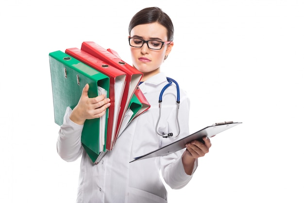 Tired young woman doctor with stethoscope holding binders in her hands in white uniform