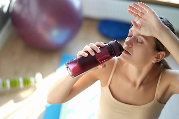 Усталая молодая женщина пьет воду после тренировки крупным планом