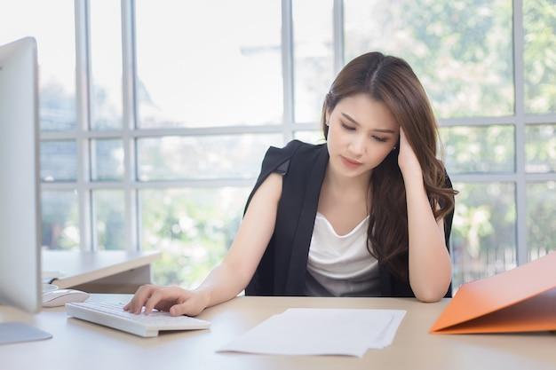 피곤한 젊은 여성은 일하는 동안 두통을 느낍니다 많은 프로젝트가 있습니다