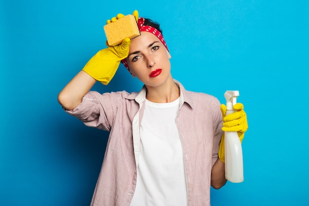 파란색 표면에 장갑에 스프레이와 스폰지를 들고 피곤 된 젊은 여자
