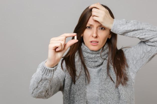 Усталая молодая женщина в сером свитере, шарфе, положив руку на голову, держа таблетку лекарства, таблетку аспирина, изолированную на сером фоне. здоровый образ жизни, лечение больных, концепция холодного сезона.