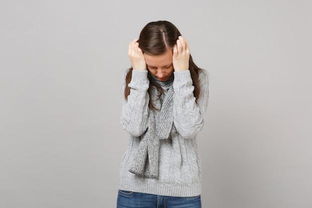 회색 스웨터를 입은 피곤한 젊은 여성, 스카프는 스튜디오의 회색 배경에 격리된 낮은 머리에 손을 얹고 있습니다. 건강한 패션 라이프 스타일 사람들은 진심 어린 감정 추운 계절 개념입니다. 복사 공간을 비웃습니다.