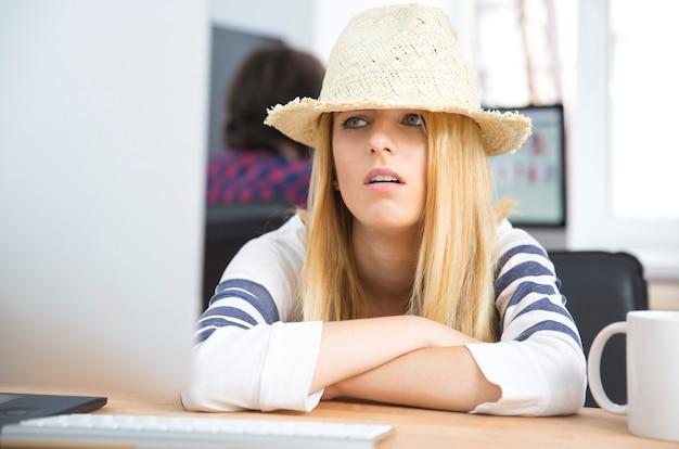 Усталая молодая женщина в шляпе сидит за столом Premium Фотографии