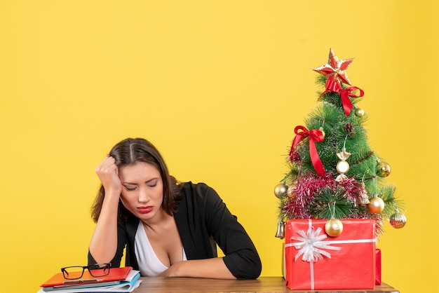 노란색에 사무실에서 장식 된 크리스마스 트리 근처 소송에서 피곤 된 젊은 여자