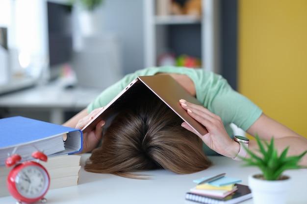 노트북으로 머리에 테이블에 피곤 된 젊은 여자 거짓말