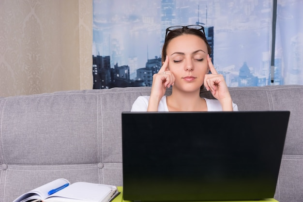 Tired young woman  making a head massage while working on a laptop and doing her business from home sitting on a sofa