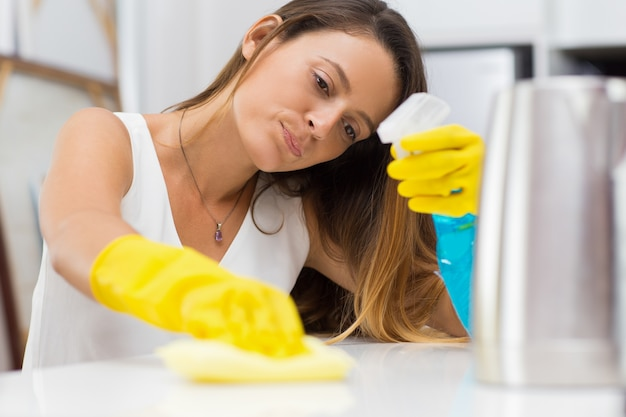 Tired young woman scrubbing table