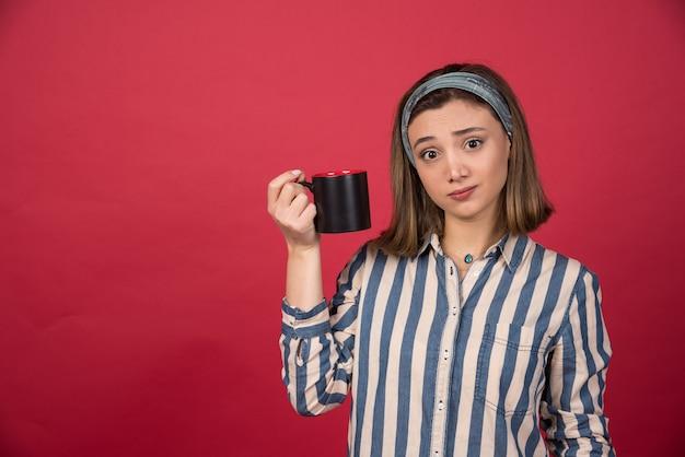 Giovane donna stanca che mostra la tazza di caffè e che posa alla parte anteriore
