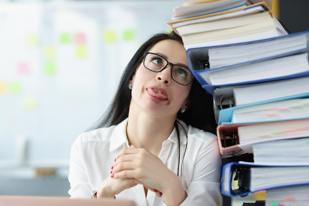 Tired young woman sitting at desk with lot of documents overwork and a lot of work concept