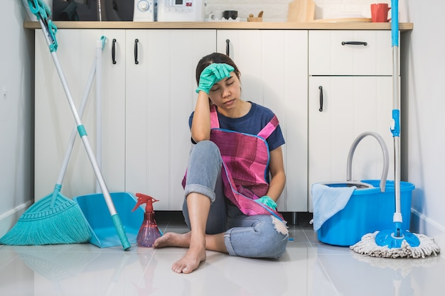 Tired young woman sitting on kitchen floor