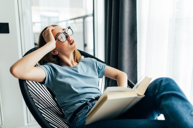Tired young woman with book sleeping on lounge chair at home