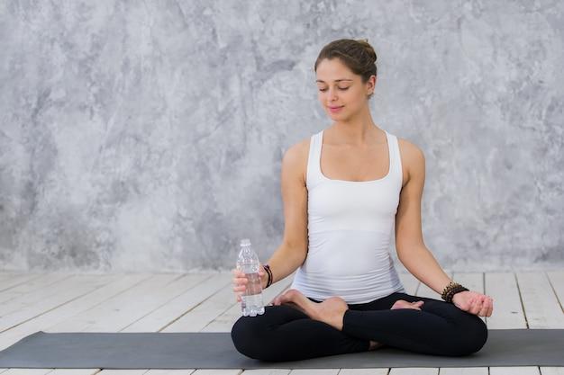 エクササイズマットに座って水を飲むスポーツウェアで疲れた若い女性