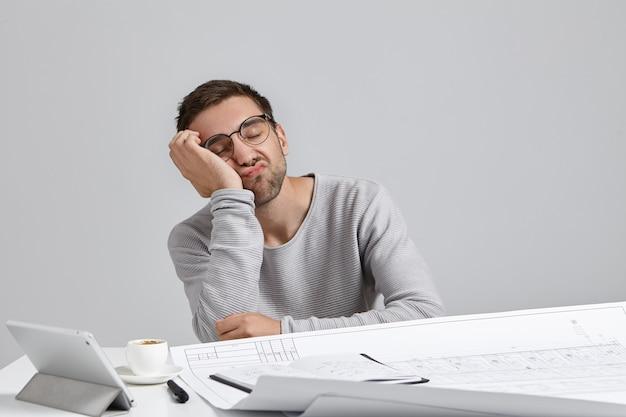 피로 개념. 피곤한 졸린 수염 난 남성 디자이너 또는 엔지니어가 손에 몸을 기울입니다.