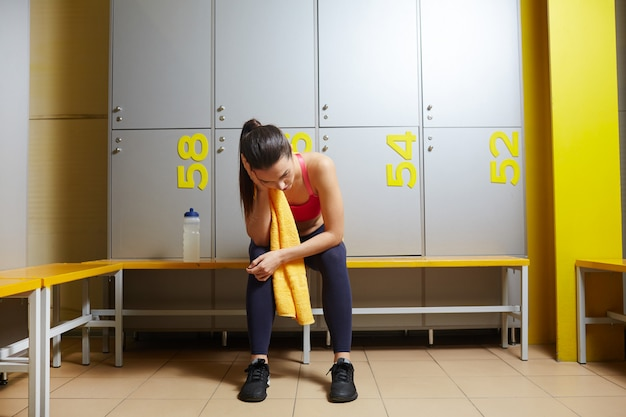 Tiredness woman in lockers room