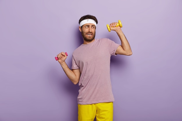 Tiredness and workout concept. displeased unshaven man raises arms with dumbbells, feels fatigue of long training, dressed in active wear