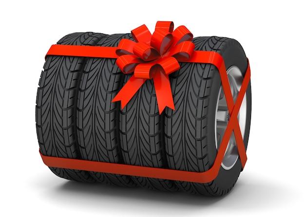ギフトとしてのタイヤディスク付きタイヤは、白い背景で隔離の赤いギフトリボンで結ばれています