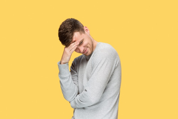 Tireserious young man with headache emotions on yellow background