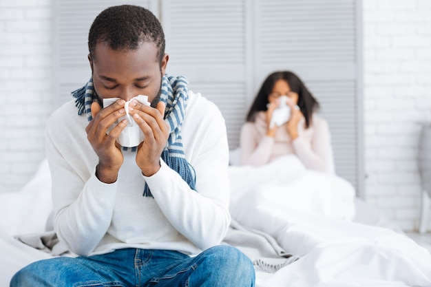 Tiresome flu. nice young couple looking unhappy while staying at home and curing their terrible flu