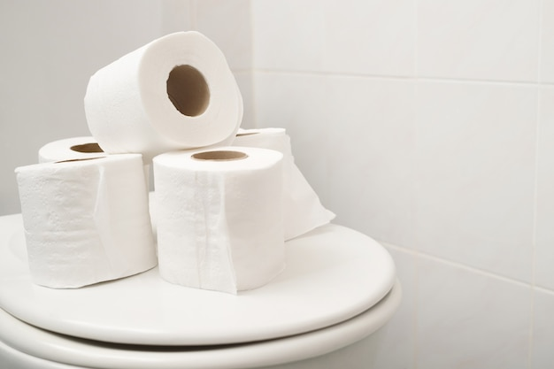 The tissue paper was placed on the toilet bowl in the bathroom.