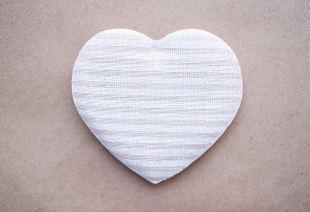 Тканевое полосатое бежевое сердце на крафт-бумаге. экологичный день святого валентина.