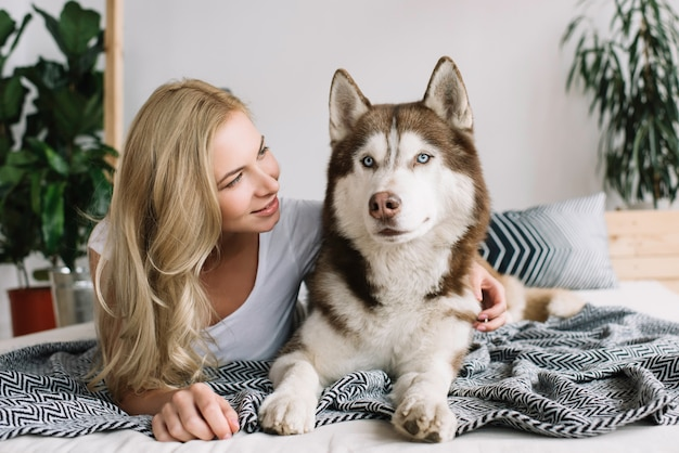 Title  beautiful happy woman with emotional smiling face lying on comfortable bed with adorable husky dog