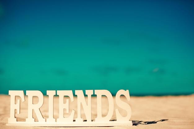 Title friends on white sand behind blue sky near ocean