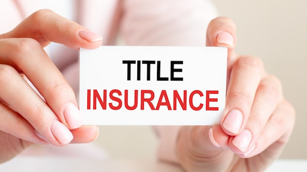 Title insurance is written on a white business card in a woman's hands