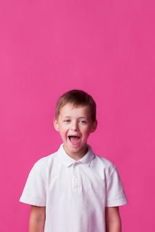 Tittle boy standing near pink wall with mouth open