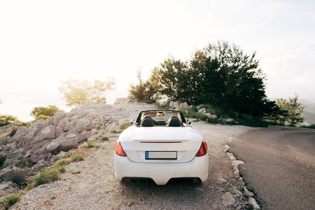 Tivat montenegro   july  white convertible with an open roof on mount lovcen in montenegro at sunset