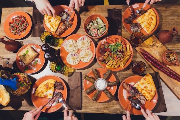 茶色の木製のテーブルにグルジア料理の上からの眺め。伝統的なグルジア料理-ヒンカリ、カルチョ、チャホフビリ、ファリ、ロビオとローカルソース-tkemali、satsebeli、adzhika。トップビュー。テキストのコピースペース