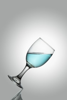 Tlted champange glass of water on white background