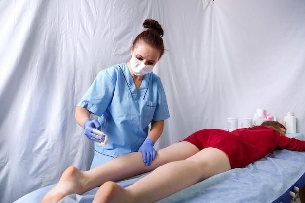 빨간 드레스를 입은 젊은 여성에게 의사 미용사가 왼쪽 다리 뒤쪽에 슈가 링을합니다.