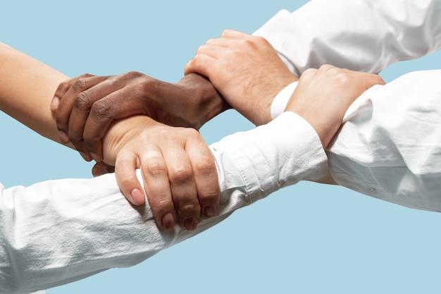 좋은 팀이되기 위해서. 팀워크 및 커뮤니케이션. 남성과 여성의 손을 잡고 블루 스튜디오 배경에 고립. 도움, 파트너십, 우정, 관계, 비즈니스, 공생의 개념.