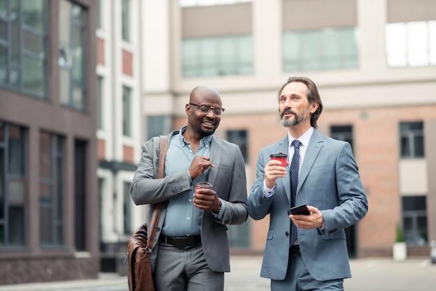 К бизнес-центру. два красивых деловых партнера вместе утром собираются в бизнес-центр