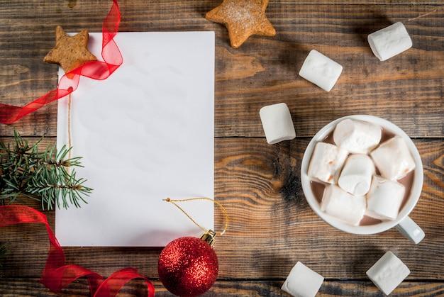 クリスマス、新年のコンセプト。木製テーブル、ウィッシュリストまたはto doリスト用ノート、ココアマグカップ、クリスマスボール、松の木、赤いリボン、マシュマロ。トップビューcopyspace