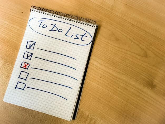 메모장 종이에 손으로 쓴 목록 체크리스트 손을 나무 테이블에 놓으십시오. . 고품질 사진