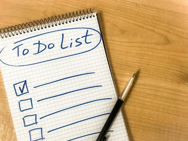 메모장 종이에 손으로 쓴 목록 체크리스트 손을 나무 테이블에 놓으십시오. penl 메모장에 누워. 고품질 사진