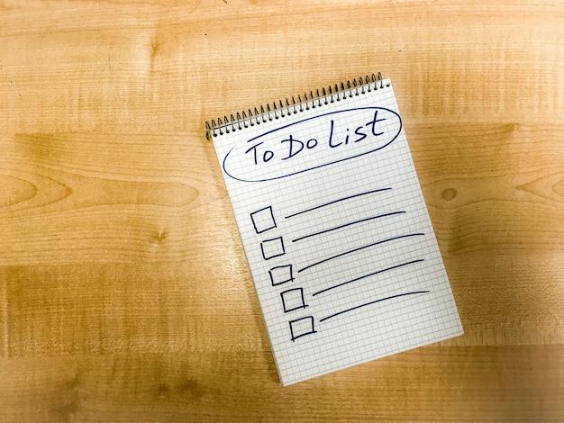 メモ帳の紙に手書きされ、コルクボードに固定されたリストを作成します。高品質の写真