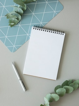 Макет списка дел. пустая страница тетради с копией пространства, ручки и ветви эвкалипта. вид сверху.