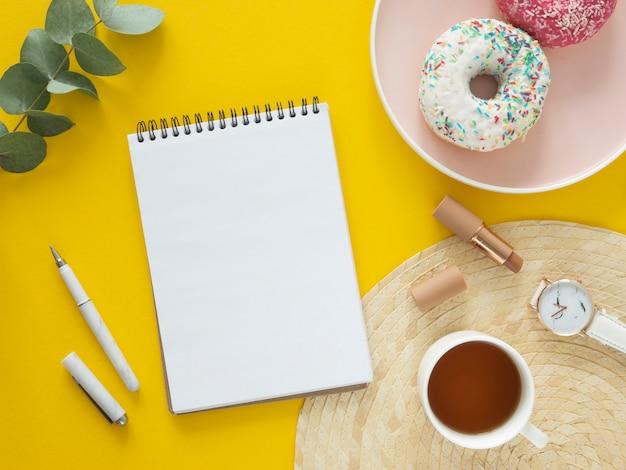 やることリストのモックアップ。トップビュー空白のノートブック、お茶、黄色のテーブルにドーナツ。フラット横たわっていた。