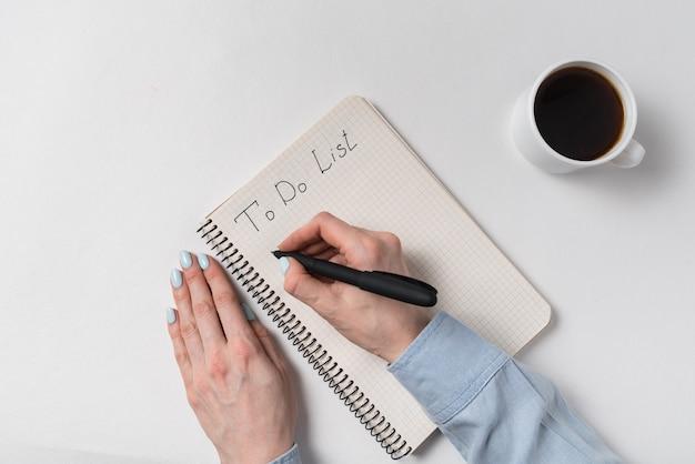 コピーブックのテキストをリストする。ノートに書く女性の手。メモ帳と一杯のコーヒー