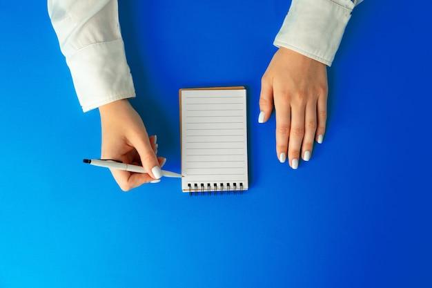 リストを行うには。ノートに書く女性の手の上から見る
