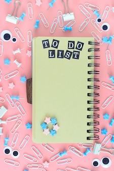 茶色のページを持つスプリングのメモ帳。碑文to doリスト。文房具は混乱しています。