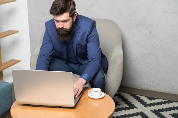 インターネット革命に参加するには、ラップトップを開く必要があります。ラップトップに取り組んでいるビジネスマン。プロのラップトップコンピューターの修理工または技術者。オフィスでラップトップを使用してひげを生やした男。