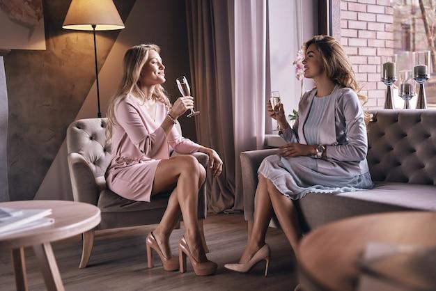 За нашу дружбу! привлекательные молодые женщины жарят друг друга и улыбаются, проводя время в современной квартире