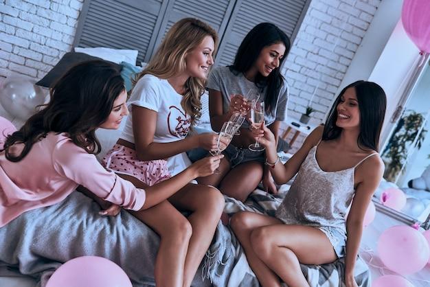 우리의 우정을 위해! 잠옷을 입고 웃고 있는 4명의 매력적인 여성이 방 전체에 풍선이 있는 침실에서 파자마 파티를 하는 동안 서로 토스트합니다