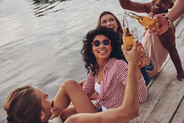 私たちの夏へ!桟橋に座って笑顔と乾杯のカジュアルな服装で幸せな若者のグループ